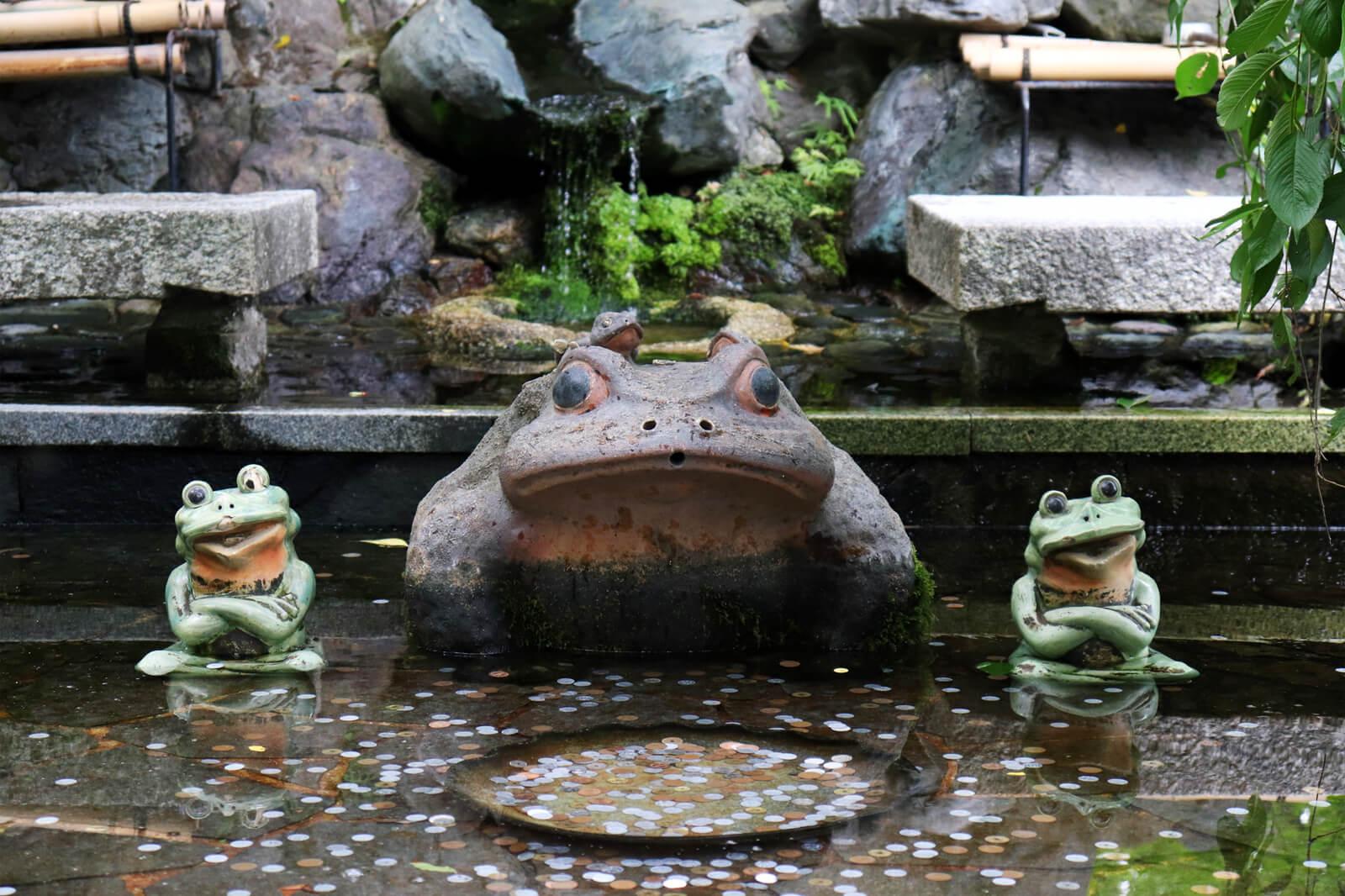 蛙の置物にお賽銭
