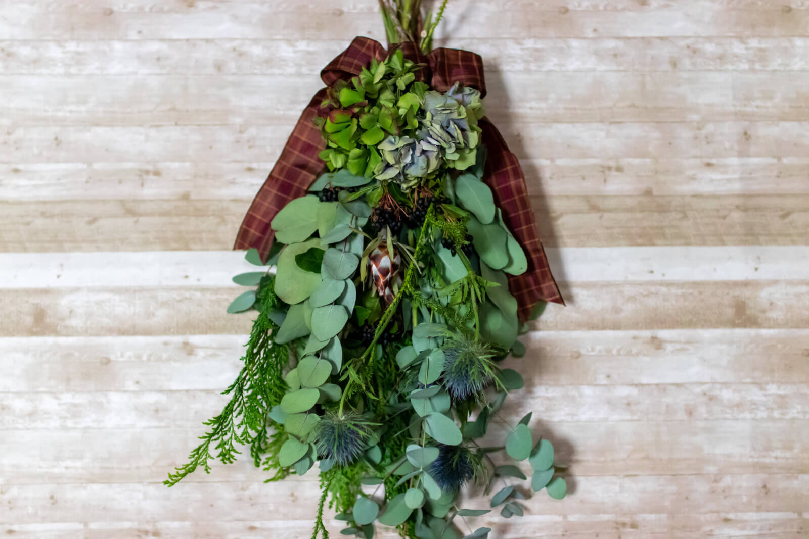 緑の花と葉をベースにしたクリスマス・スワッグの正面