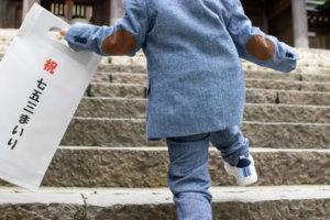 七五三参りの袋を持つスーツ姿の3歳男児