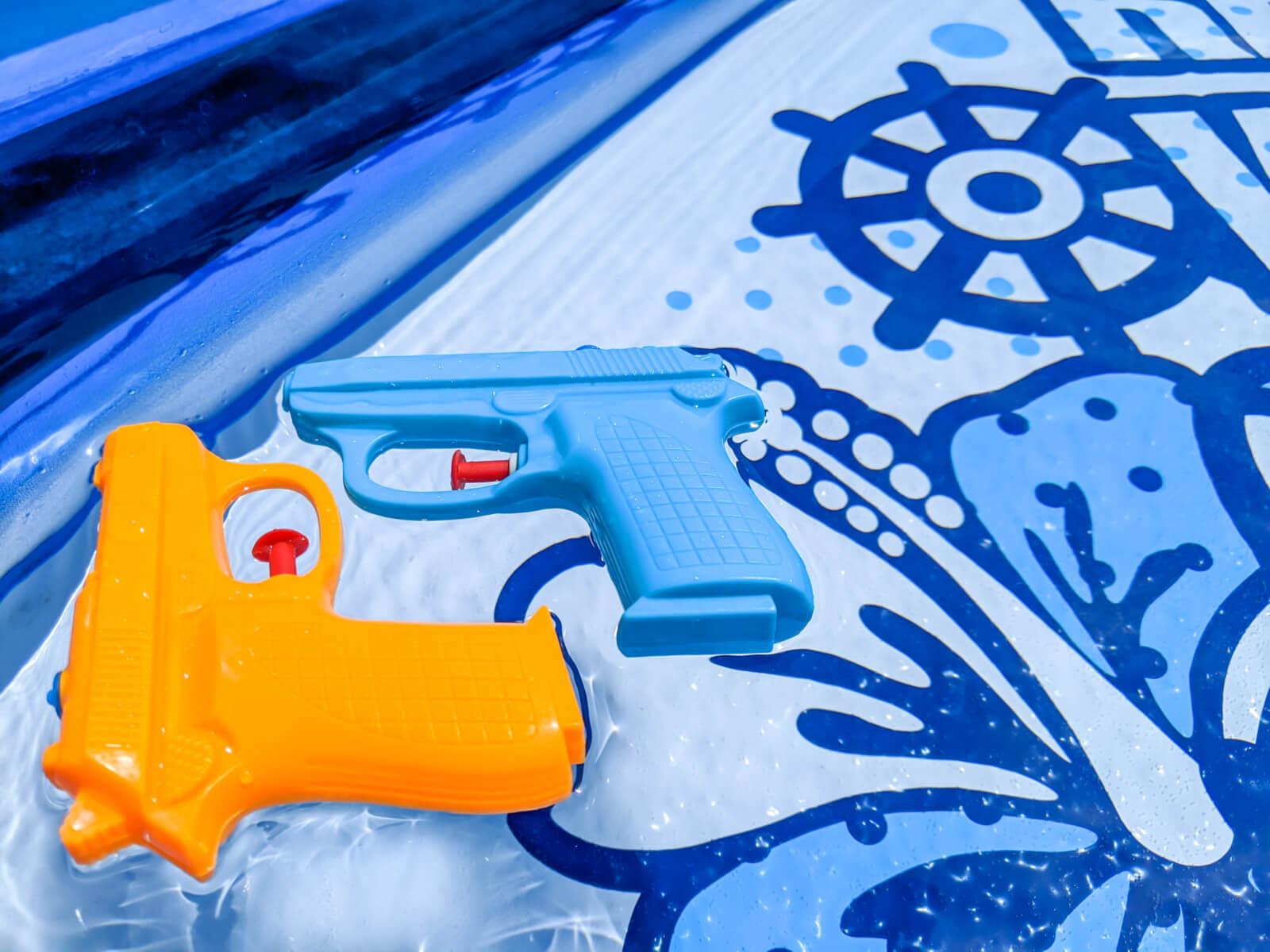 プールに浮かぶ水鉄砲2つ